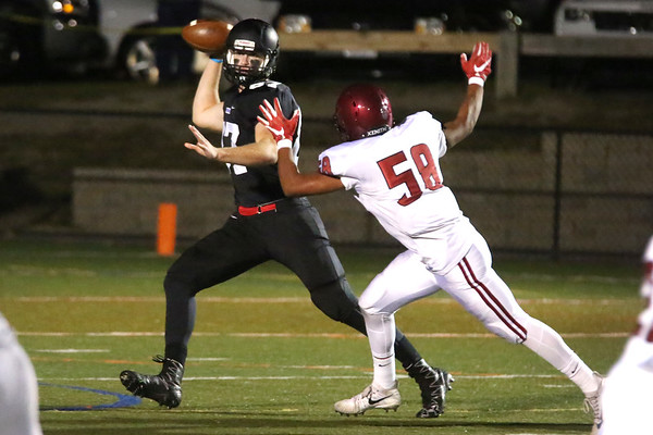 HADLEY GREEN/Staff photo<br /> Marblehead's Andy Clough (87) throws the ball while Gloucester's Carlos Hernandez Reyes (58) plays defense at the Marblehead v. Gloucester varsity football game at Marblehead High School. 10/13/17