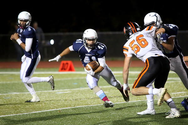 HADLEY GREEN/Staff photo<br /> Peabody's Angel Paulino (41) pivots around Beverly defenders at the Peabody v. Beverly football game at Peabody High School.<br /> <br />  10/20/17