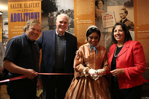 """HADLEY GREEN/Staff photo<br /> From left, Salem Museum Director David Goss, Creative Director Ken Harris, actress Kathy-Ann Hart, playing the role of Salem abolitionist Sarah Parker-Remond, and Salem Mayor Kim Driscoll officially unveil a new display at the Salem Museum,  titled """"Salem, Slavery & Abolition."""" The display is open to the public until the museum closes for the season on October 31st. <br /> <br />  10/18/17"""