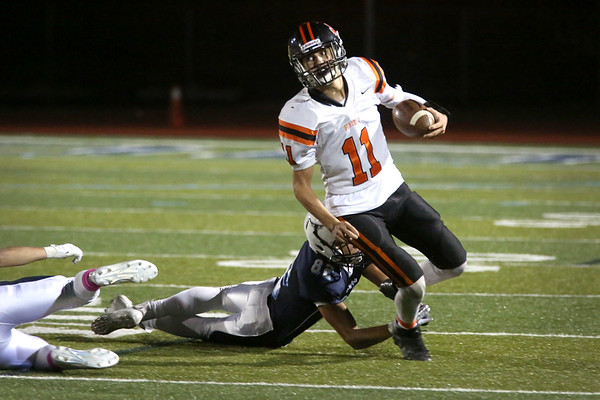 HADLEY GREEN/Staff photo<br /> Beverly's Ryan Barror (11) runs with the ball while Peabody's Ramon Franco (82) tries to tackle him at the Peabody v. Beverly football game at Peabody High School.<br /> <br />  10/20/17