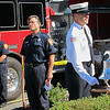 "With Danvers Fire Department chaplain Marc Santorella, middle, standing at attention, fire prevention officer Lt. James Brooks rings a ""last alarm"" outside of Fire Department Headquarters on High Street during a ceremony to honor the first responders who died in the Sept. 11, 2001, attacks.<br /> Photo by Ethan Forman/The Salem News, Tuesday, Sept. 11, 2012."