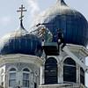 KEN YUSZKUS/Staff photo. Ismael Diaz and Durim Cela, behind him, scrape, caulk, and paint the Saint Nicholas Orthodox Church in Salem   9/12/14