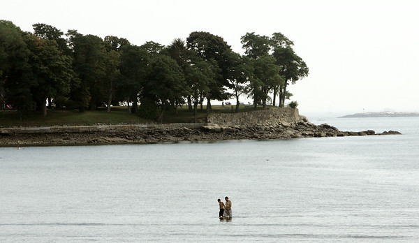 KEN YUSZKUS/Staff photo. Two people walk in the shallow ocean near Lynch Park in Beverly.