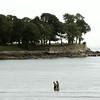 KEN YUSZKUS/Staff photo. Two people walk in the shallow ocean near Lynch Park in Beverly.