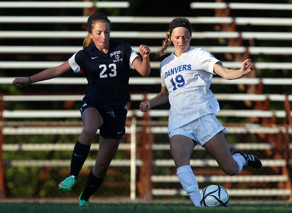 Danvers senior Meaghan McKenna (19) tries to play the ball upfield while being pressured closely by Swampscott freshman Julianna Rhoads (23) during the first half of play on Wednesday afternoon. DAVID LE/Staff photo. 9/3/14.