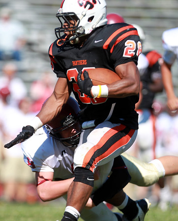 Gloucester junior linebacker Mike Cody holds on tight to the legs of Beverly running back Matt Madden (28). The Fishermen fell to the Panthers 30-16 in NEC action on Saturday morning. DAVID LE/Staff photo. 9/27/14.