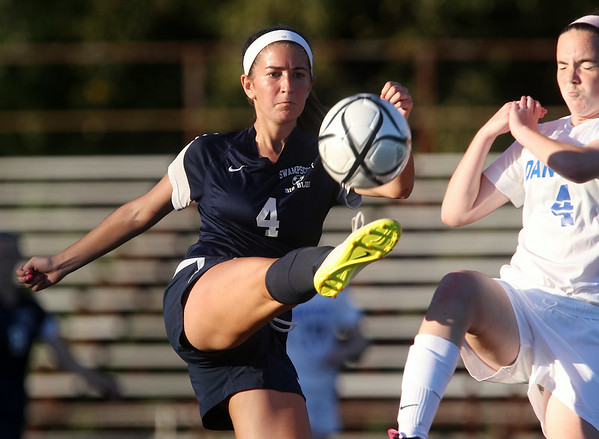 Swampscott junior Jess Gambale (4) concentrates on the ball as Danvers freshman Shannon Mansfield (4) applies pressure. DAVID LE/Staff photo. 9/3/14.