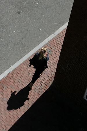 KEN YUSZKUS/Staff photo. A pedestrian and her shadow walk along New Liberty Street in Salem.   9/17/14