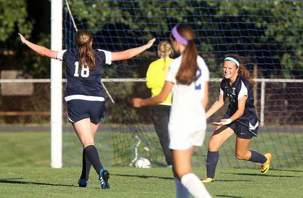 Swampscott junior Meghan Hartmann (19) right, excitedly runs towards sophomore teammate Jaymie Caponigro (18) after Hartmann scored the Big Blue's first goal of the game against Danvers. DAVID LE/Staff photo. 9/3/14.