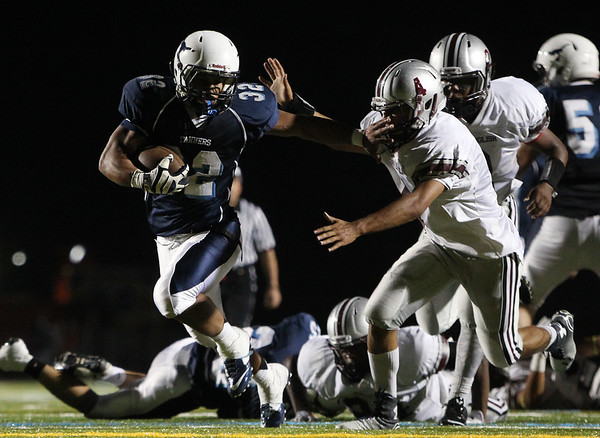 Peabody junior running back Doug Santos (32) stiff arms Lynn English senior CJ Hernandez (4) en route to a long first half touchdown run. DAVID LE/Staff photo. 9/12/14.