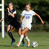 Danvers senior captain Emily Murphy (10) carries the ball upfield while being pursued by Swampscott sophomore Jaymie Caponigro (18) on Wednesday afternoon. DAVID LE/Staff photo. 9/3/14.