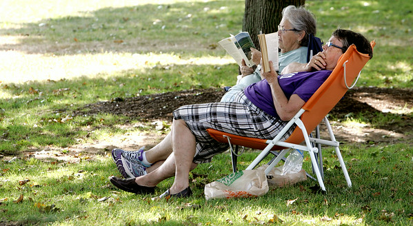 KEN YUSZKUS/Staff photo. Maureen Barnes, left, and Gail Penny, both of Beverly, sit and read in the cool shade under trees at Dane Street Beach in Beverly.