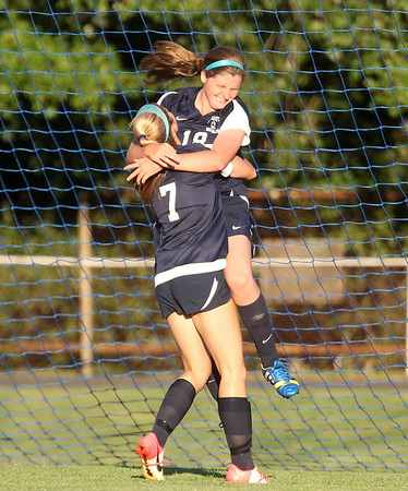 Swampscott sophomore Jaymie Caponigro (18) leaps into the arms of junior teammate Bailey Shorr (7) as they celebrate Caponigro's first half goal against Danvers. DAVID LE/Staff photo. 9/3/14.