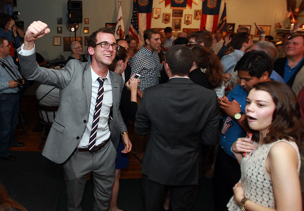 Seth Moulton supporters Paul Bologna, left, pumps his fist in the air in celebration as Alissa Heller, right, can't believe the news that incumbent Congressman John Tierney conceded the race in the 6th district on Tuesday evening. DAVID LE/Staff photo. 9/9/14.