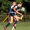 Danvers senior Meaghan McCarriston, left, manages to kick the ball just past lunging Swampscott sophomore Bridget Cullinane, during the first half of play on Wednesday afternoon. DAVID LE/Staff photo. 9/3/14.