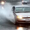 KEN YUSZKUS/Staff photo.    A car plows through a large puddle on Bridge Street near Boston Street in Salem.   9/30/15.