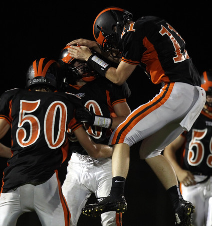 DAVID LE/Staff photo. Ipswich freshman Billy Shaw (80) gets mobbed by teammates Shane Grady (11) and Matt Collyer (50) after Shaw's sack of North Reading quarterback Nick Colangelo to end the first half of play. 9/11/15.