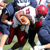 DAVID LE/Staff photo. Gloucester tailback Jermaine Edward (33) plows forward while dragging along Swampscott senior Dante Ceccarelli (7). 9/26/15.