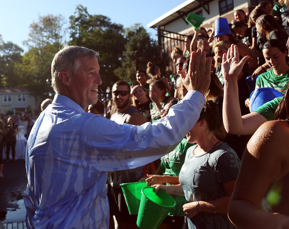 DAVID LE/Staff photo. John Frates gives out high fives and thank you's to Endicott College students who came out to participate in the Ice Bucket Challenge following the dedication of Frates Hall on campus. 9/13/16.