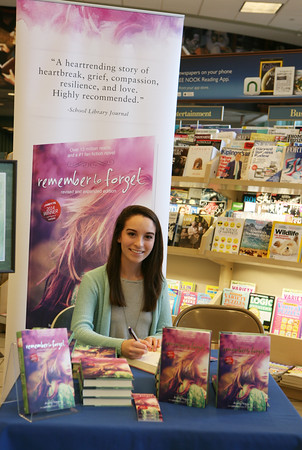 """AMY SWEENEY/Staff photo.<br /> Ashley Royer, 17, a senior at Peabody High School signs her book """"remember to forget"""" at Barnes & Noble in Peabody."""