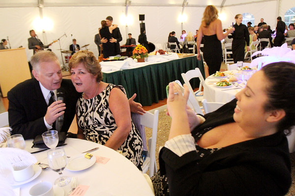 Kathy Hitchcock sings with Mad House's John Keegan as her co-worker Eleni Webb records the moment during the SeniorCare Gala dinner Wednesday, September 21, at Misselwood. Photo by Nicole Goodhue Boyd