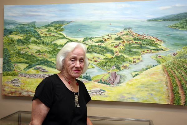 AMY SWEENEY/Staff photo.<br />  Beverly artist Avis Thomas stands in front of the painting she did of how Beverly might have looked in the early 18th century. It was part of a new exhibit by the Beverly Historical Society at the John Cabot House.<br /> Opening Sept. 8, 2016<br /> John Cabot House<br /> Beverly
