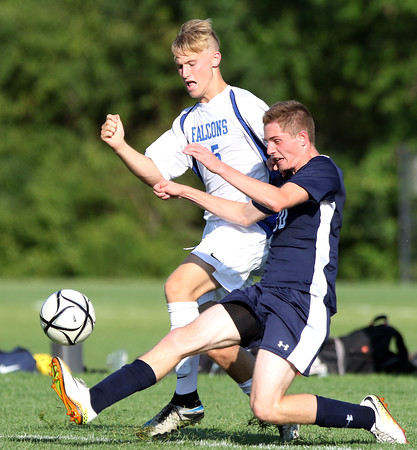 DAVID LE/Staff photo. Swampscott's Thomas O'Keefe, right, makes a sliding challenge to knock the ball away from Danvers' Jay McPherson, left. 9/8/16.