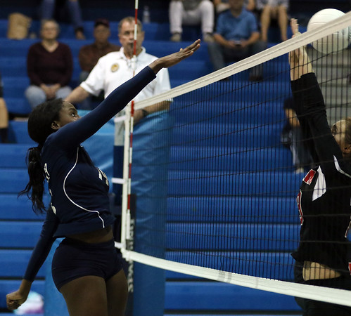 DAVID LE/Staff photo. Peabody's Chinenye Onwuogo smashes the ball past the outstretched hands of a blocker for Salem. 9/27/16.