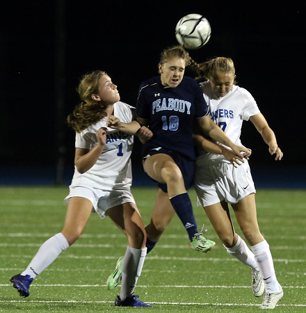 DAVID LE/Staff photo. Peabody forward Brianna Gaynor (18) leaps through Danvers juniors Lydia Runnals (1) and Jess Barthelmess (27) to win a header. 9/20/16.