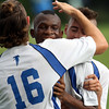 DAVID LE/Staff photo. Danvers' Sherak Ayamga, center, gets mobbed by his teammates after tapping home the Falcons first goal of the game. 9/8/16.