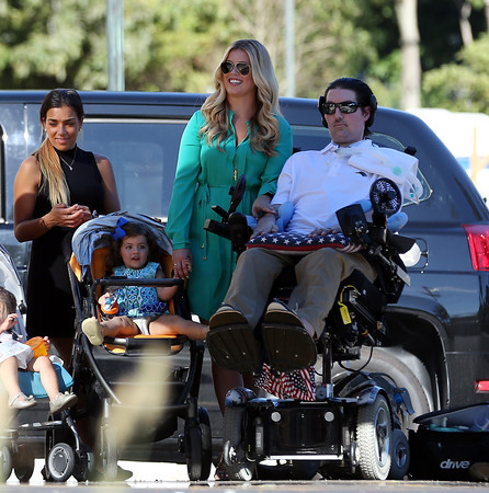 DAVID LE/Staff photo. Pete, Julie, and daughter Lucy Frates, hold hands during a dedication ceremony for Peter Frates Hall on the campus of Endicott College in Beverly. 9/13/16.