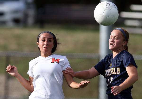 DAVID LE/Staff photo. Marblehead senior Meg McCarthy, left, plays the ball past a Lynnfield defender and looks to get past her. 9/8/16.