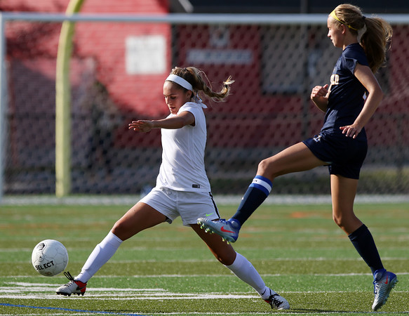 DAVID LE/Staff photo. Marblehead sophomore Annie Migliore, left, stretches to keep control the the ball while being pressured by a Lynnfield player. 9/8/16.