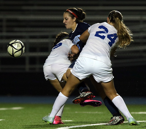 DAVID LE/Staff photo. Peabody forward Marissa Orlando, center, tries to get to the ball while being sandwiched by Danvers sophomores Madison Pesce, left, and Jess Pelletier (24). 9/20/16.