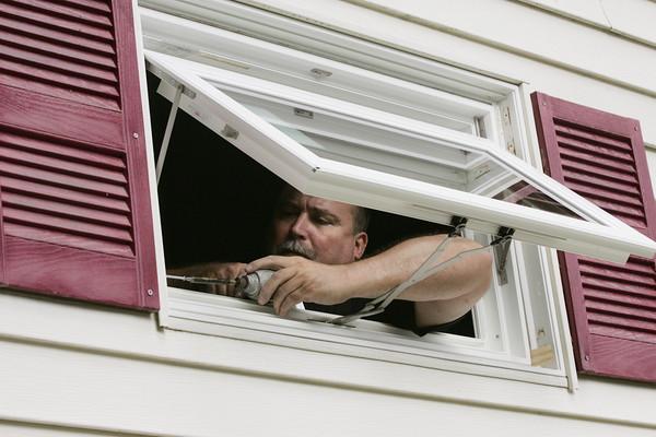 KEN YUSZKUS/Staff photo.     Alan Vedope of Lynnfield installs window as part of the Habitat for Humanity redo at 5 Sanborn Street in Peabody     09/14/16