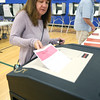KEN YUSZKUS/Staff photo   Pat Kee of the 5th precinct places her ballot into the ballot box at the Vye gym at Danvers High School.    09/08/16