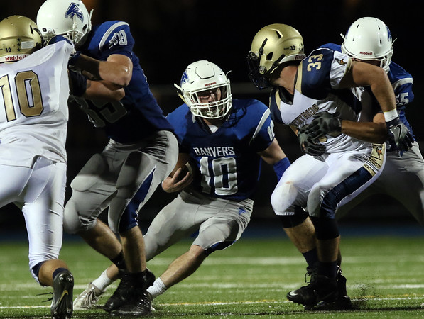 DAVID LE/Staff photo. Danvers senior Matt Andreas looks for running room against Winthrop on Friday evening. 9/9/16.
