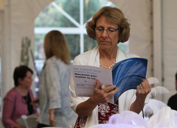Pam Constantine of Harborlight Community Partners looks over a program for the evening.<br /> Photo by Nicole Goodhue Boyd