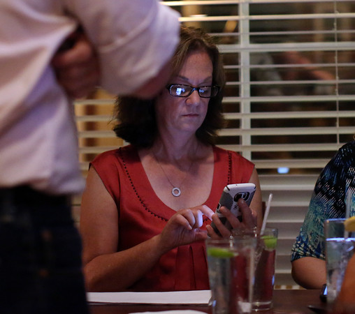 DAVID LE/Staff photo. Republican candidate for Essex County Sheriff Anne Manning-Martin, right, checks polling while sitting at a table surrounded by supporters at her election party held at Kelley Square Pub in Peabody on Thursday night. Manning-Martin got the Republican nomination after beating out the other candidates. 9/8/16.