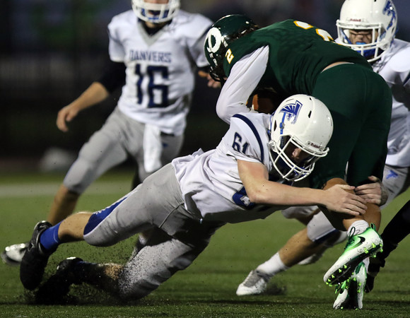 DAVID LE/Staff photo. Danvers senior Jack Ackerley drags down Lynn Classical running back Chase Buono (2) for a solo tackle. 9/30/16.