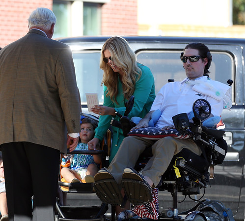 DAVID LE/Staff photo. Julie Frates smiles after receiving a door with Pete's number 3 on it from Dr. Richard Wylie, while holding hands with her daughter Lucy Frates,  during a dedication ceremony for Peter Frates Hall on the campus of Endicott College in Beverly. 9/13/16.