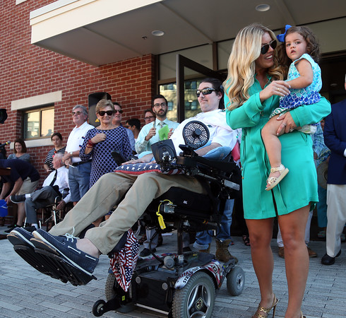 DAVID LE/Staff photo. Pete Frates, with his wife Julie and daughter Lucy, walk out to loud applause from Endicott College students for an Ice Bucket Challenge. 9/13/16.