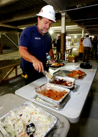 """KEN YUSZKUS/Staff photo  Windover/Beverly Crossing project superintendent Scott Martin digs into the barbeque lunch at the """"topping off"""" ceremony for the new apartment complex, Windover/Beverly Crossing, at 131 Rantoul Street in Beverly.    09/06/16"""