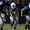 DAVID LE/Staff photo. Danvers junior Justin Mullaney (2) looks for running room against Winthrop on Friday evening. 9/9/16.