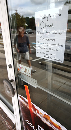 KEN YUSZKUS/Staff photo.  A sign on the front door of the Dunkin' Donuts in Hamilton reads it is closed due to water concerns.   9/27/16