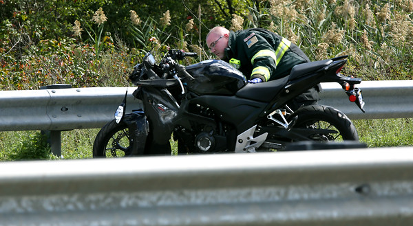 KEN YUSZKUS/Staff photo.     Danvers firefighter Jeffrey Snow looks over a motorcycle involved in a crash on Route 128 North just before Route 62.     09/15/16