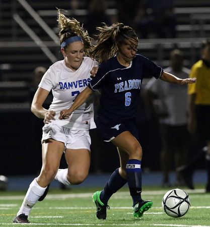 DAVID LE/Staff photo. Peabody junior captain Emily Nelson plays the ball across the field while being pressured by Danvers senior captain Nicole White. 9/20/16.