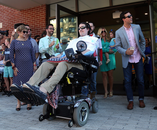 DAVID LE/Staff photo. Pete Frates walks out to a loud roar from Endicott students, while flanked by his brother Andrew, right, following a dedication ceremony for Peter Frates Hall on the campus of Endicott College in Beverly. 9/13/16.