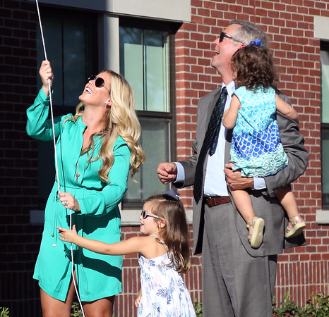 DAVID LE/Staff photo. Julie Frates, wife of Pete Frates unveils the Peter Frates Hall sign on the brand new residence hall at Endicott College, named in honor of Frates. 9/13/16.