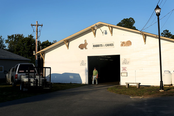 HADLEY GREEN/Staff photo<br /> A man walks through the rabbits and cavies barn at the Topsfield Fair fairgrounds. The fair opens on September 29th.<br /> 09/07/17